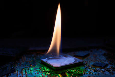 The flame is on the central processor that lies on the printed circuit board. Low-key photo.