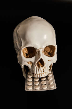 A Pharmaceutical blister pack in the jaw of a human skull model. Low-key photo.