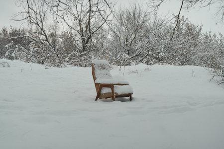 A forsaken chair on a snow.