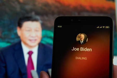 SARANSK, RUSSIA - MARCH 22, 2021: The smartphone with Joe Biden contact seen on it's screen and Xi Jinping seen on the background.