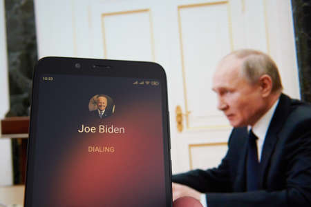SARANSK, RUSSIA - MARCH 22, 2021: The smartphone with Joe Biden contact seen on it's screen and Vladimir Putin seen on the background.