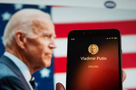 SARANSK, RUSSIA - MARCH 22, 2021: The smartphone with Vladimir Putin contact seen on it's screen and Joe Biden seen on the background. Redactioneel