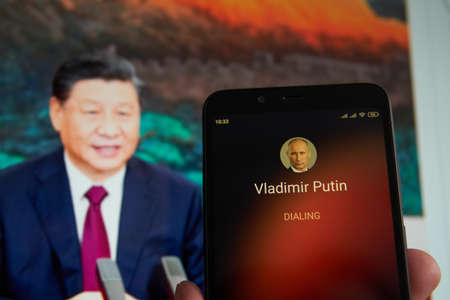 SARANSK, RUSSIA - MARCH 22, 2021: The smartphone with Vladimir Putin contact seen on it's screen and Xi Jinping seen on the background.