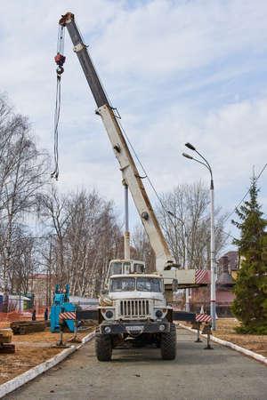 Saransk, Russia - April 11, 2021: Truck-mounted crane at chassis of Ural-4320. Truck-mounted crane at construction works. Redactioneel