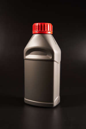 Canister with brake fluid on a black background. Stockfoto