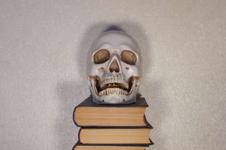 Human skull model with a softgel in the jaw on a stack of books.