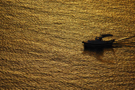 Boat in sunset visible in water, trails, rich yellow and orange color  photo