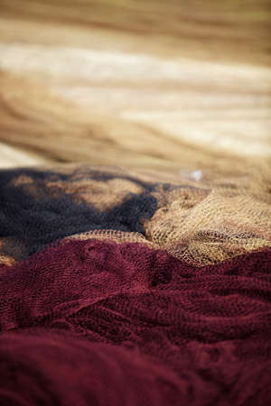 Fishing net in 3 colors laying on ground, sharp foreground, blurry background photo