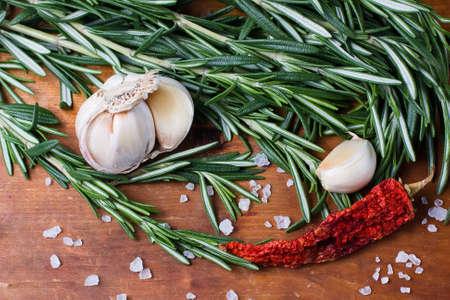 chiles picantes: Romero fresco, ajo y pimientos picantes sobre fondo de madera vieja Foto de archivo