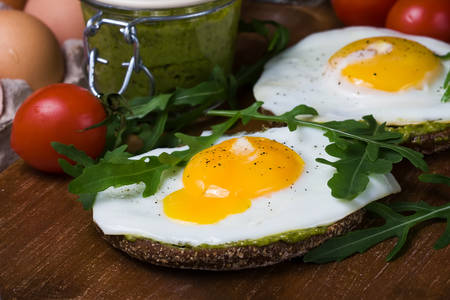 toasted sandwich: croque-madame with fried egg , pesto sauce and rucola, close up. Traditional French Toasted Sandwich Stock Photo