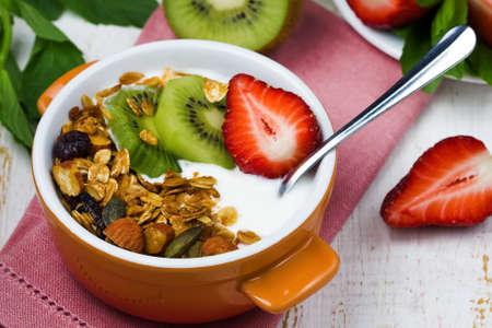 yogur: desayuno con frescos griego yogur, fresas, kiwi y granola en una mesa de madera blanca