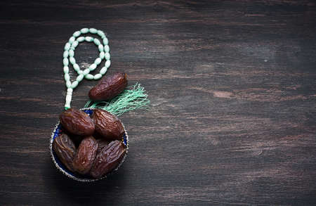 Dates fruit and rosary still life, on a dark wooden background