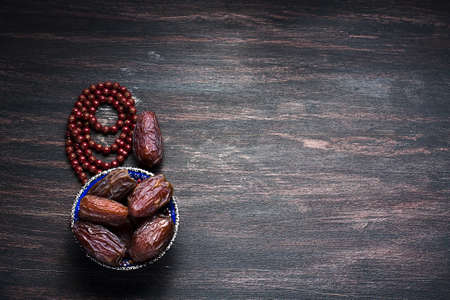 date: Dates fruit and rosary still life, on a dark wooden background