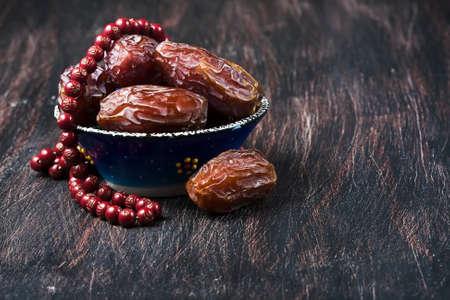 comida arabe: Fechas de frutas y rosario todavía vida, sobre un fondo de madera oscura