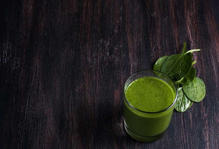 Green spinach smoothie on wooden board