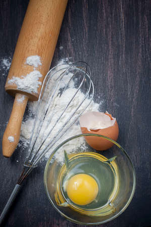 haciendo pan: Flour and eggs on a wooden table, means for making bread