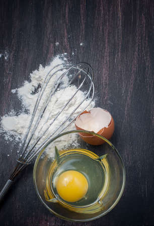 making bread: Flour and eggs on a wooden table, means for making bread
