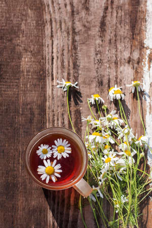 cup of chamomile tea with chamomile flowers, old wood table background