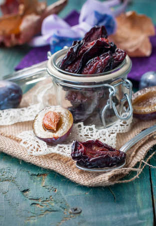 Dried plums  in a transparent jar. Selective focus