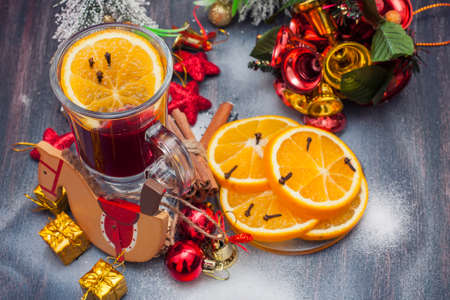 vin chaud: Hot wine (mulled wine) with spices on wooden background. Selective focus.
