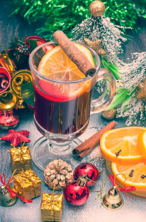 vin chaud: Hot wine (mulled wine) with spices on wooden background. Stylization. Selective focus. Banque d'images