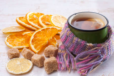 convalesce: Сup of hot tea with lemon and scarf.  Lemon and orange slices, pieces of sugar. Selective focus