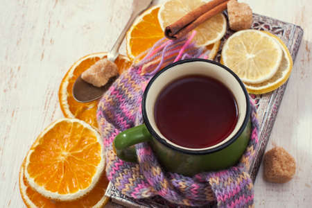 convalesce: Сup of hot tea with lemon and scarf. Winter time. Selective focus Stock Photo