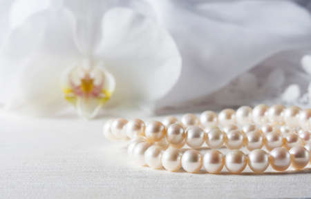 White pearl necklace on handmade lace background. Photo toned, selective focus.
