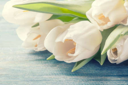 bouquet of white tulips on a wooden background. Selective focus, toned photo Stock Photo