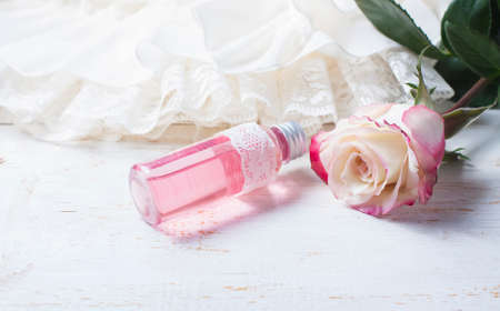 perfume oil: perfumed rose water in a bottle on a wooden table.  Selective focus