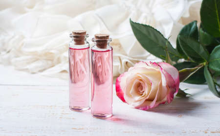 perfumed: perfumed rose water in a bottle on a wooden table.  Selective focus