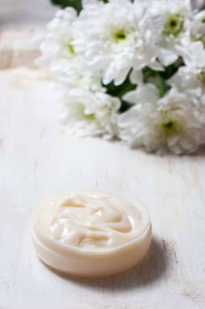 aroma facial: Natural facial cream, with chrysanthemum on white wooden background. Selective focus
