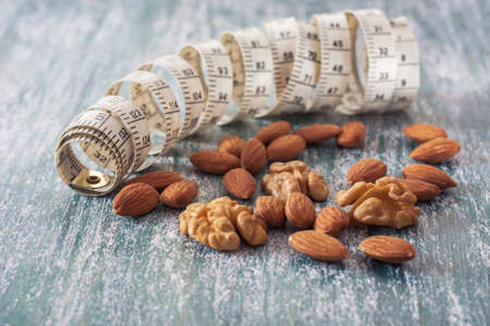 metro medir: The concept of a healthy lifestyle, nuts  and measuring meter. Selective focus Foto de archivo