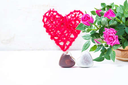 Valentines Day with chocolates, decorative heart and pink roses. Selective focus