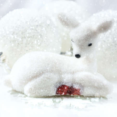 Small white deer and christmas decorations white background. copy space, soft focus