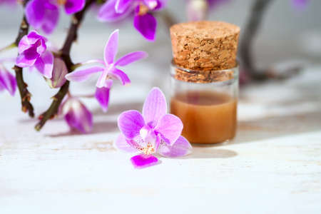 spa setting with cosmetic cream, gel and purple orchid on white wooden table background. Selective focus