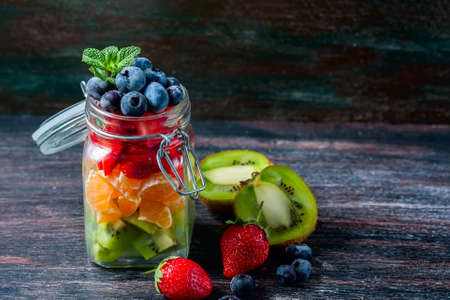 Healthy homemade fruit salad in a jar on rustic wooden background. Healthy food, Diet, Detox or Vegetarian concept. Selective focus