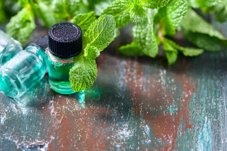 bath essence: Essential oil of peppermint in small bottles, fresh green mint on wooden background, selective focus