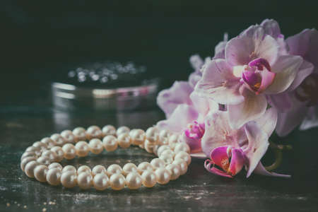jewerly: Pink orchid with a pearl necklace. Photo toned, selective focus. Stock Photo