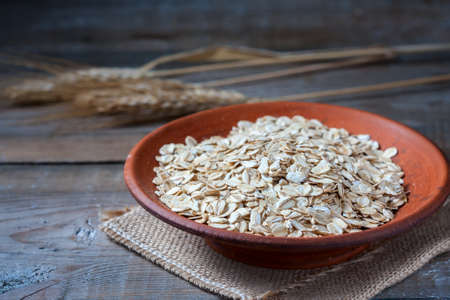 Oat flakes on a on wooden table, selective focus Stock Photo