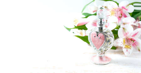 perfumery concept: Luxurious perfume bottle with flowers on white background. Feminine beauty concept. Selective focus