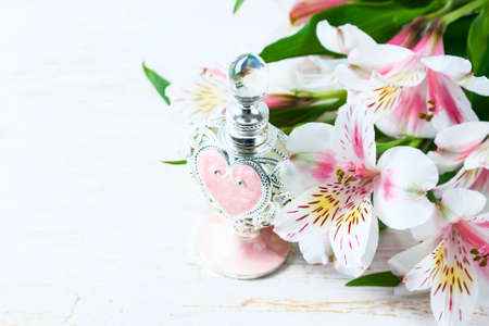 Luxurious perfume bottle with flowers on white background. Feminine beauty concept. Selective focus