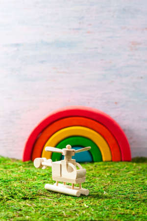 Wooden toys - a helicopter and a rainbow on the grass. selective focus Stock Photo