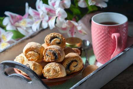 white backing: Homemade breakfast: rolls and cup of tea on vintage serving tray. Selective focus