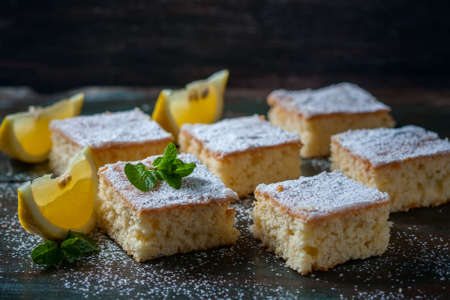 Fresh homemade sweet cake for breakfast with slices of lemon and mint on wooden board. Selective Focus Stock Photo