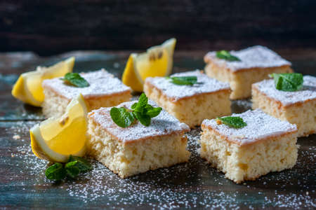 pie de limon: Fresh homemade sweet cake for breakfast with slices of lemon and mint on wooden board. Selective Focus Foto de archivo