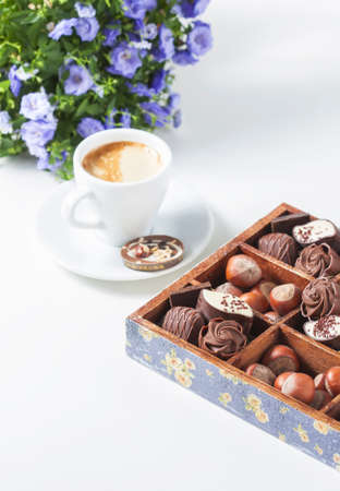 Cup of coffee on a white background with a variety of chocolates in a wooden box. Selective focus