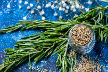 branches of fresh rosemary, dried rosemary in a glass jar on a dark blue background , selective focus Stock Photo