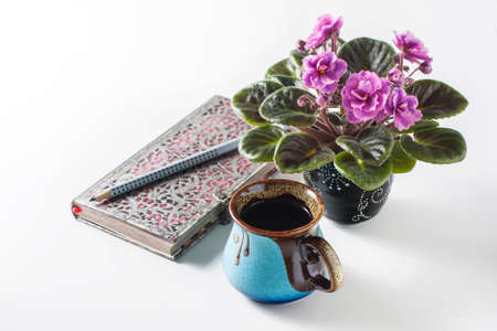 Breakfast. Coffee, clean notebook and African Violet. Female working desk. Selective focus Stock Photo