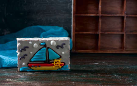 christmas cake: Homemade homemade gingerbread cookie in the shape of a boat on the dark dark wooden background. Selective focus.